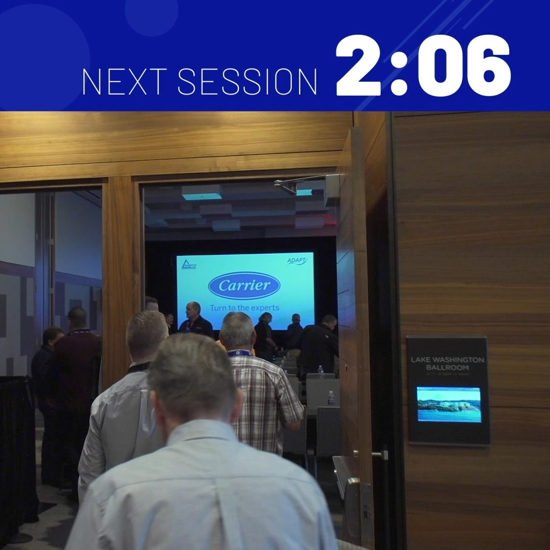 frame from an event bumper video with a timer countdown to the next session and people walking into a conference room