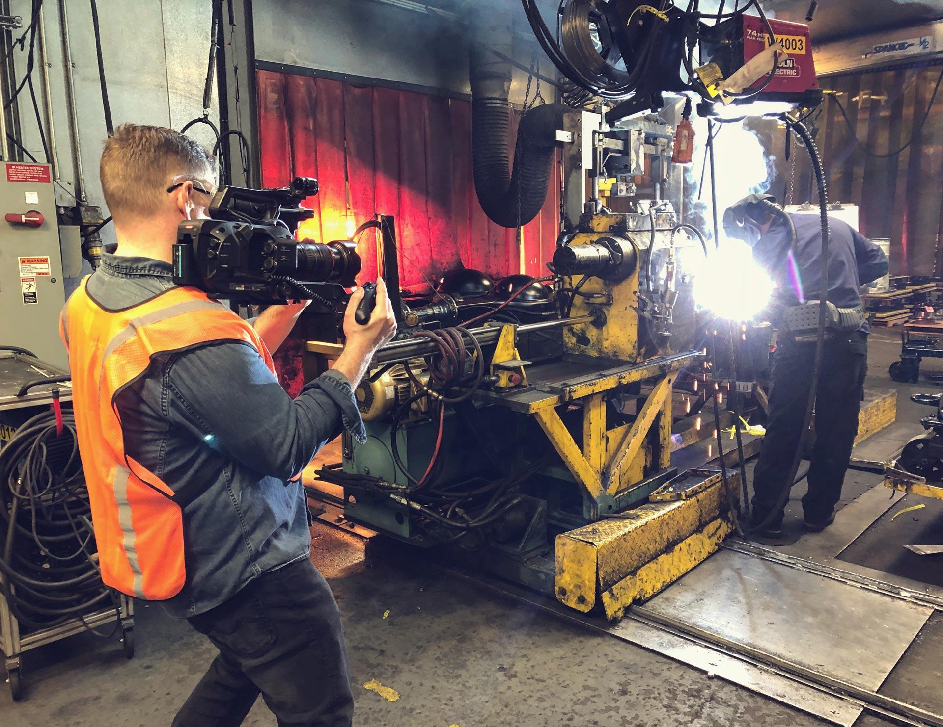 a cameraman in an orange vest filming a welder manufacturing an engine