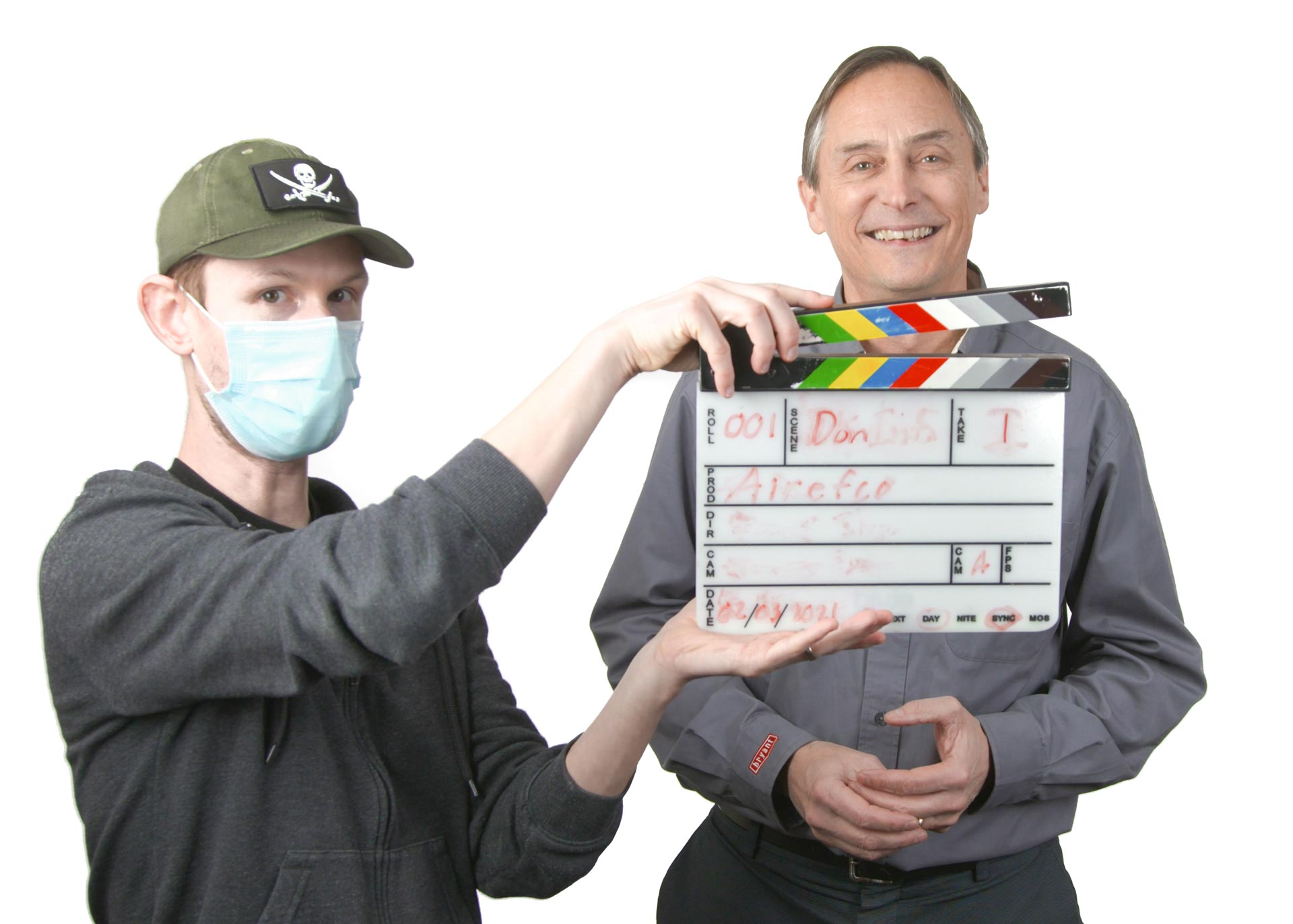 An A C holding up a slate in front of an interview subject standing in front of a stark white background on a video production set
