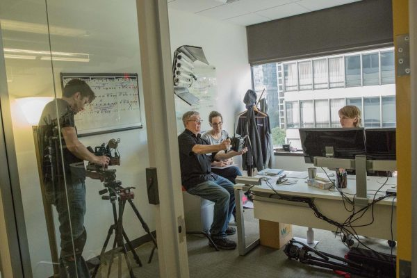 a director, producer and DP filming an actress in a small office