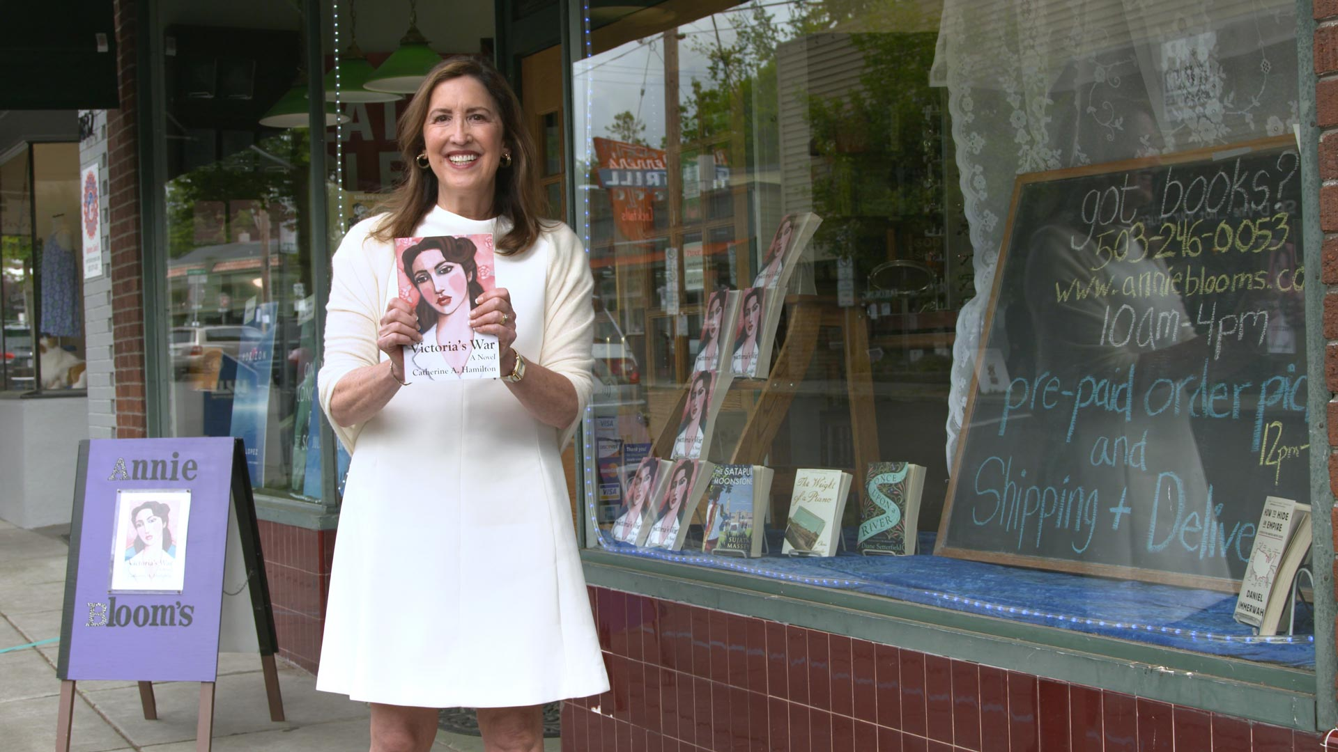 Frame from a video with Catherine Hamilton holding her book, Victoria's War, in front of Annie Bloom's Books