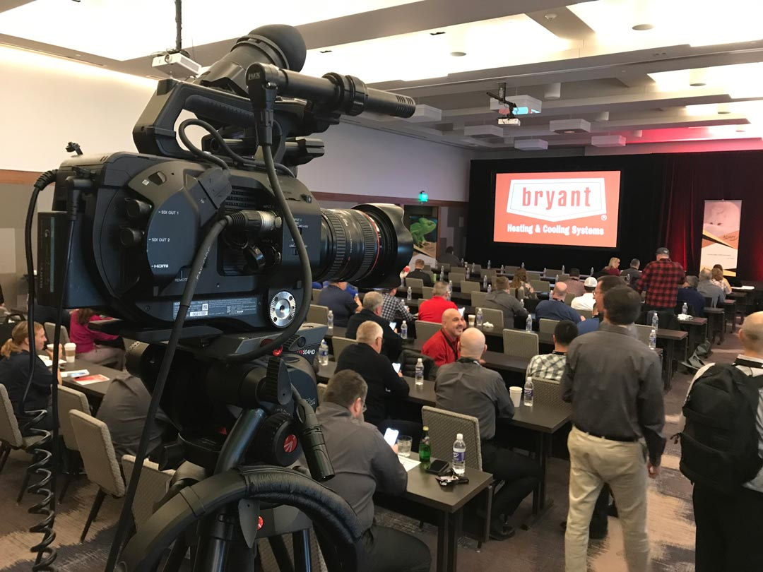 video camera in the back of an event room with a large Bryant logo on the screen in front of a crowd of people at an Airefco dealer meeting