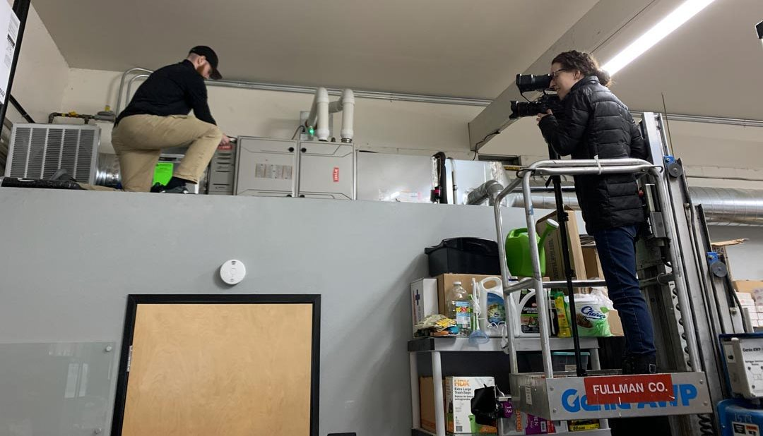 VideoPro camera operator standing in a lift filming a Bryant technician working on an AC unit above a small business building interior doorway