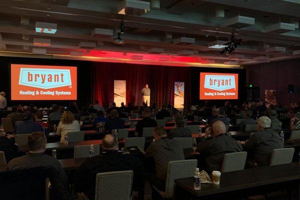 the Airefco Bryant dealer meeting in a ballroom in Seattle with the Bryant brand on large screens in the front of a large seated audience
