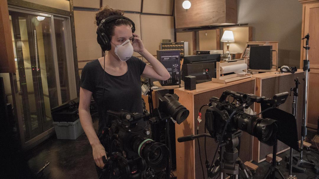 a camera operator wearing a mask for Covid-19 checks sound in headphones while standing behind two cameras inside a sound studio