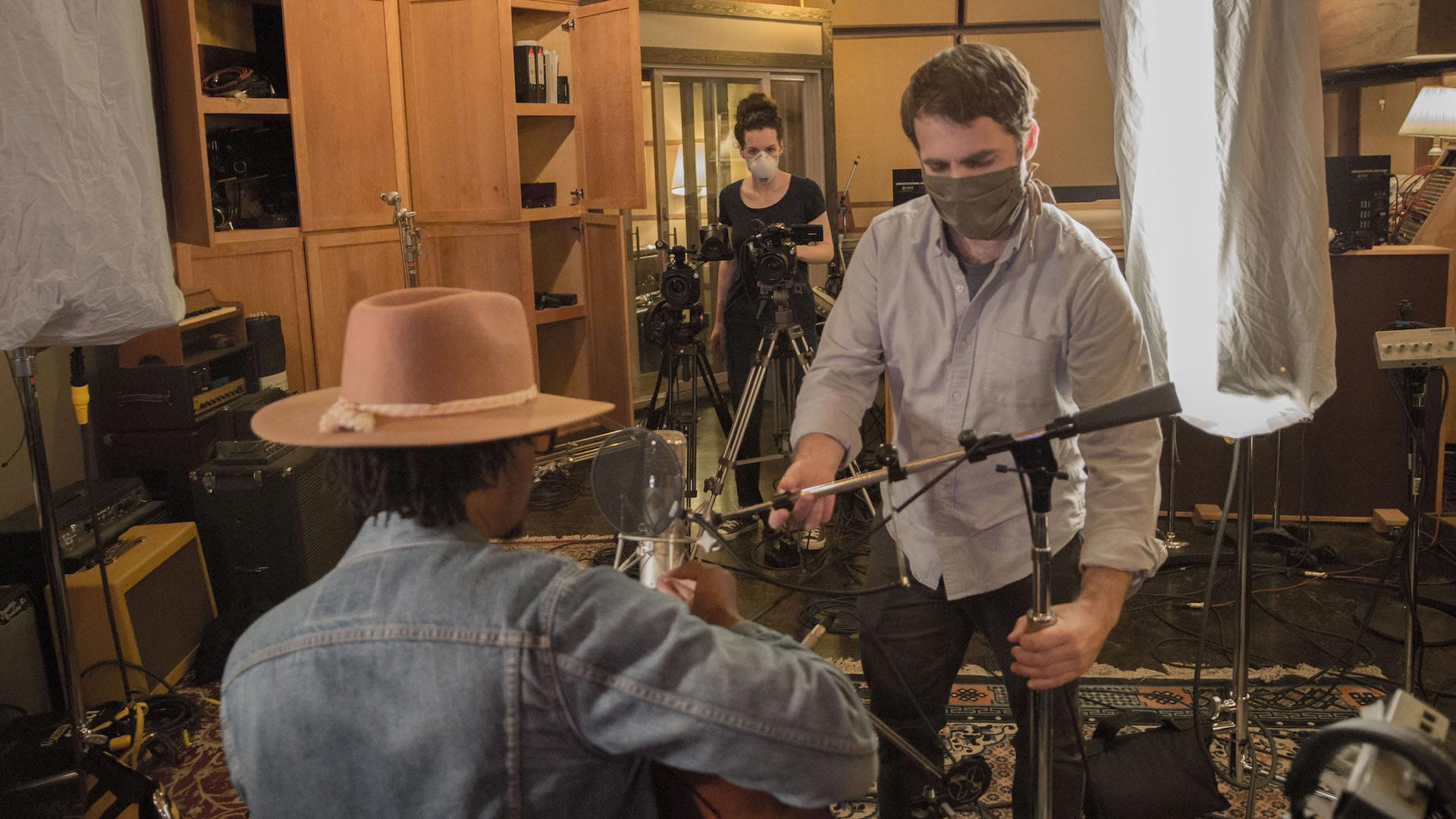 a sound engineer adjusts a microphone for a musician while a camera operator adjusts a video camera in the background inside a sound studio filming session